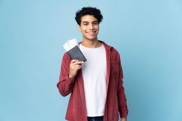 Giovane venezuelano isolato su blu felice in vacanza con passaporto e biglietti aerei