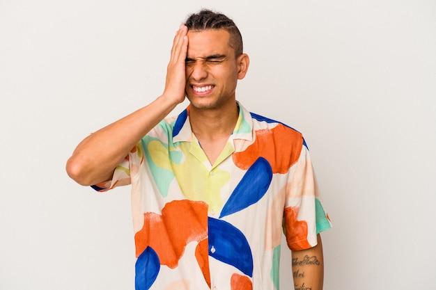Giovane uomo venezuelano isolato su sfondo bianco dimenticando qualcosa, schiaffeggiando la fronte con il palmo e chiudendo gli occhi.