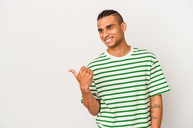 Il giovane venezuelano isolato su sfondo bianco punta con il dito pollice lontano, ridendo e spensierato.