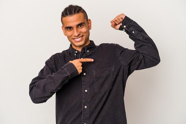 Giovane uomo venezuelano isolato su sfondo bianco che mostra un gesto di forza con le braccia, simbolo del potere femminile