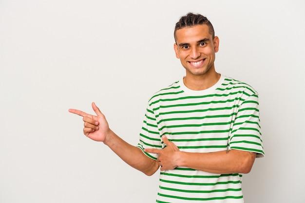 Giovane uomo venezuelano isolato su sfondo bianco sorridente allegramente puntando con l'indice lontano.