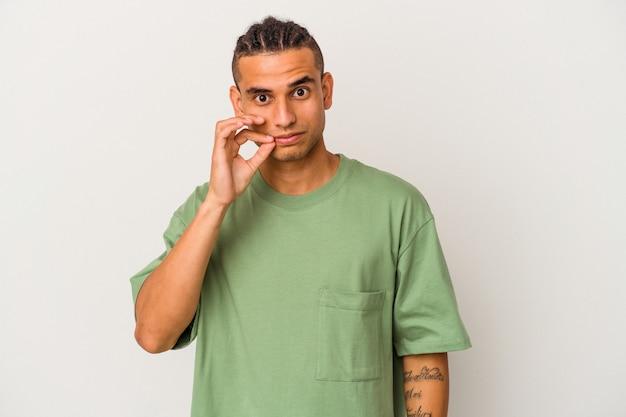 Giovane uomo venezuelano isolato su sfondo bianco con le dita sulle labbra mantenendo un segreto.