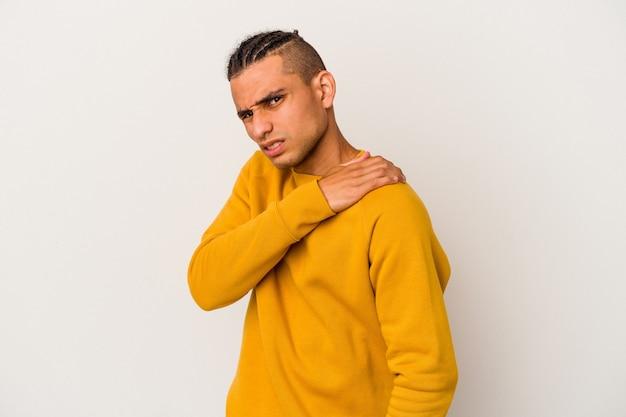 Giovane uomo venezuelano isolato sulla parete bianca che ha un dolore alla spalla.
