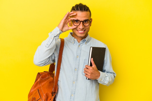 Giovane studente venezuelano isolato su sfondo giallo eccitato mantenendo il gesto ok sull'occhio.