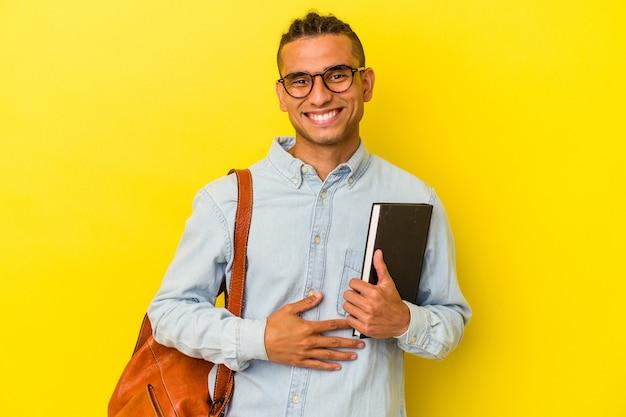 Giovane studente venezuelano isolato su sfondo giallo che ride e si diverte.
