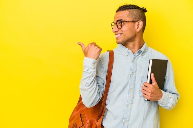 Il giovane studente venezuelano isolato su sfondo giallo punta con il pollice lontano, ridendo e spensierato.