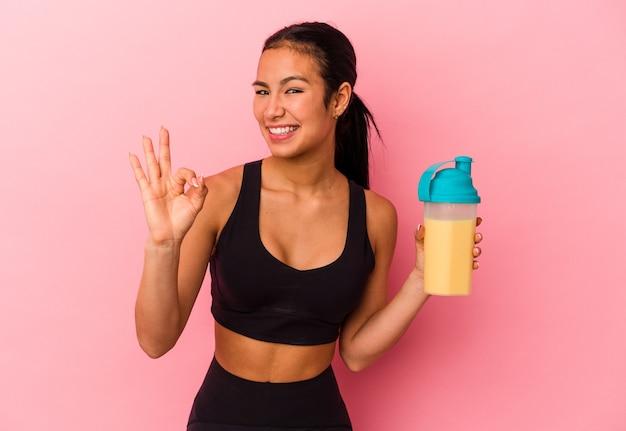 Giovane donna venezuelana che beve un frullato proteico isolato su sfondo rosa