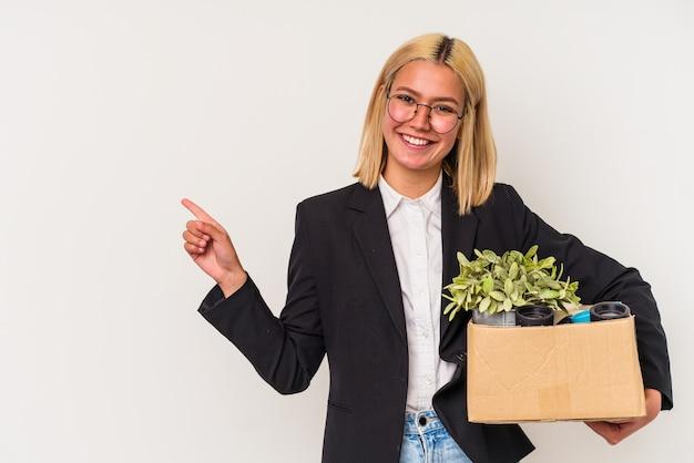 Giovane donna venezuelana licenziata dal lavoro isolato su sfondo bianco sorridendo e indicando da parte, mostrando qualcosa in uno spazio vuoto.