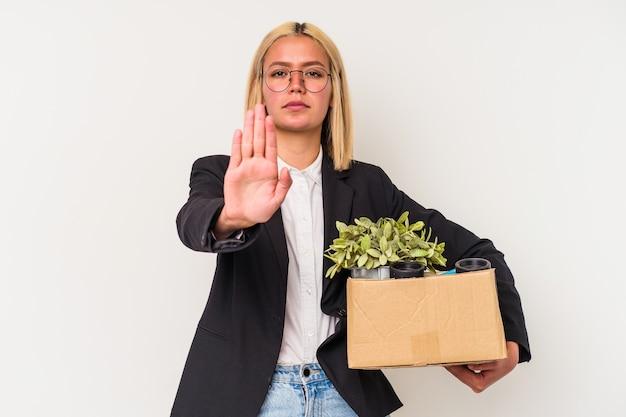 Giovane donna venezuelana licenziata dal lavoro isolato sul muro bianco in piedi con la mano tesa che mostra il segnale di stop, impedendoti.