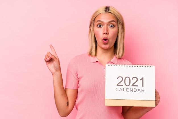 Giovane donna venezuelana che tiene un calendario isolato su sfondo rosa che punta al lato
