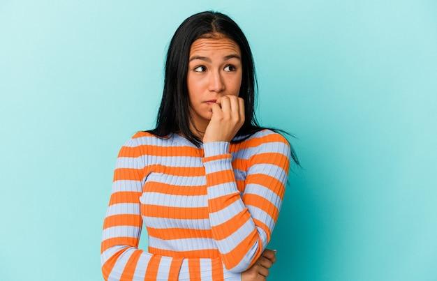 Giovane donna venezuelana isolata su sfondo blu che si morde le unghie, nervosa e molto ansiosa.