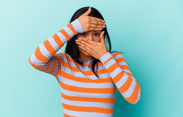 La giovane donna venezuelana isolata su sfondo blu sbatte le palpebre verso la telecamera attraverso le dita, imbarazzata che copre il viso.