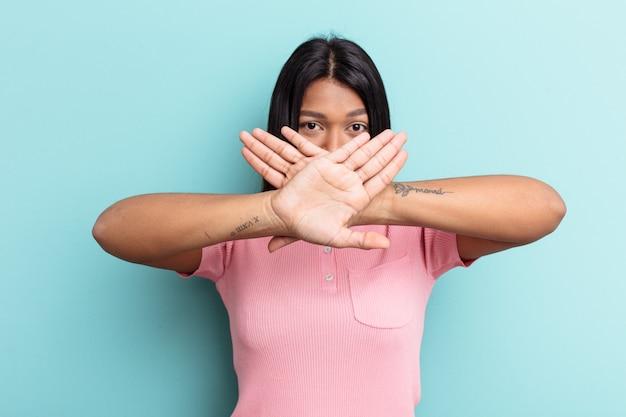 Giovane donna venezuelana isolata su sfondo blu che fa un gesto di rifiuto