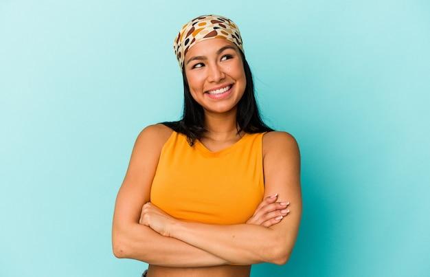 Giovane donna venezuelana isolata su sfondo blu che sogna di raggiungere obiettivi e scopi