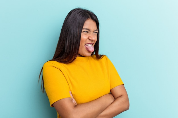 Giovane donna venezuelana isolata su sfondo blu divertente e amichevole con la lingua fuori.