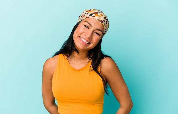 Giovane donna venezuelana isolata su sfondo blu felice, sorridente e allegra.
