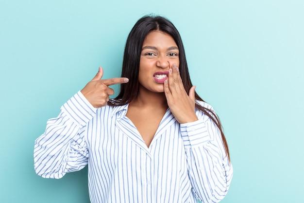 Giovane donna venezuelana isolata su sfondo blu con un forte dolore ai denti, dolore molare.