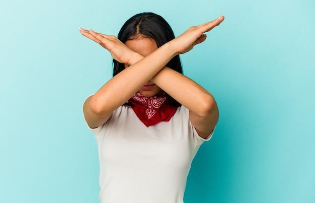 Giovane donna venezuelana isolata su sfondo blu mantenendo due braccia incrociate, concetto di negazione.