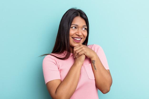 La giovane donna venezuelana isolata su sfondo blu tiene le mani sotto il mento, sta guardando felicemente da parte.