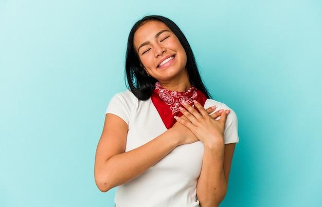 Giovane donna venezuelana isolata su sfondo blu che ride tenendo le mani sul cuore, concetto di felicità.