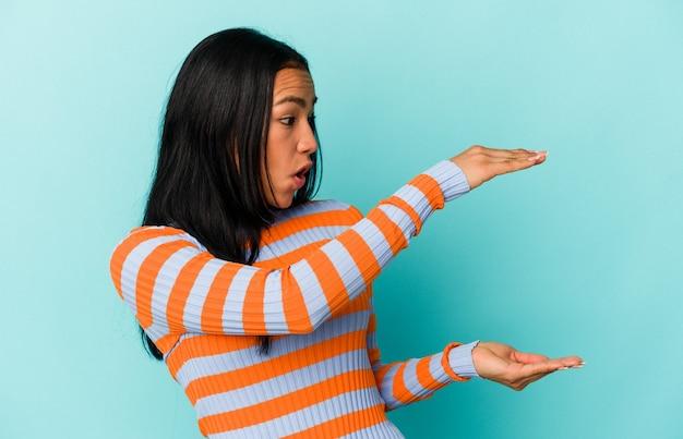 Giovane donna venezuelana isolata su sfondo blu scioccata e stupita in possesso di uno spazio di copia tra le mani.