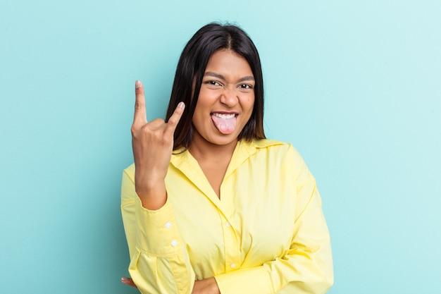 Giovane donna venezuelana isolata su sfondo blu che mostra il gesto rock con le dita