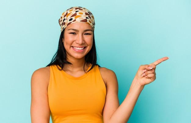 Giovane donna venezuelana isolata su sfondo blu che sorride allegramente puntando con l'indice lontano.