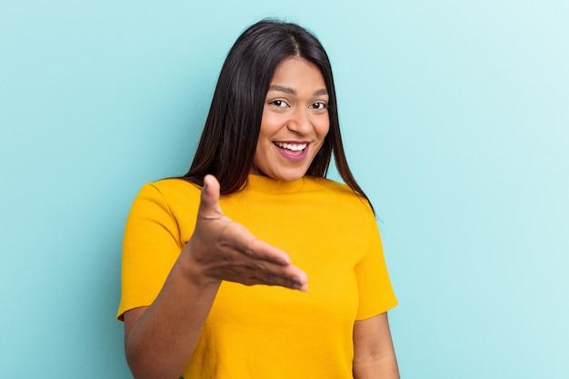 Giovane donna venezuelana isolata su sfondo blu allungando la mano alla telecamera nel gesto di saluto.