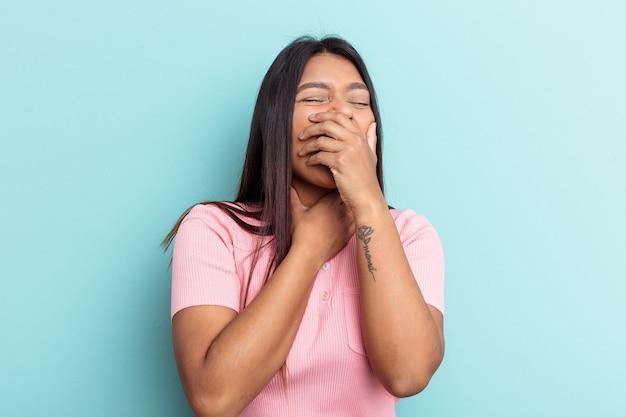 La giovane donna venezuelana isolata su sfondo blu soffre di dolore alla gola a causa di un virus o di un'infezione.
