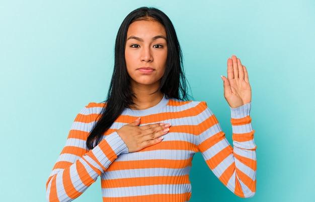 Giovane donna venezuelana isolata su sfondo blu prestando giuramento, mettendo la mano sul petto.