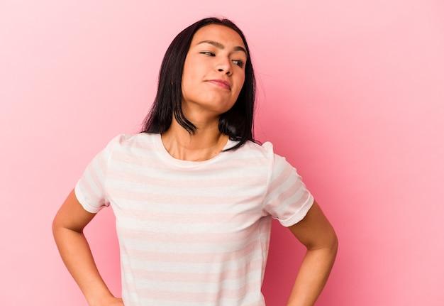 Giovane donna venezuelana isolata su sfondo rosa che sogna di raggiungere obiettivi e scopi