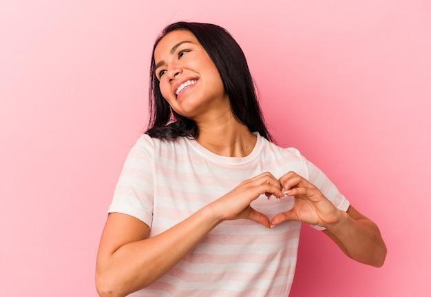 Giovane donna venezuelana isolata su sfondo rosa sorridente e che mostra una forma di cuore con le mani.