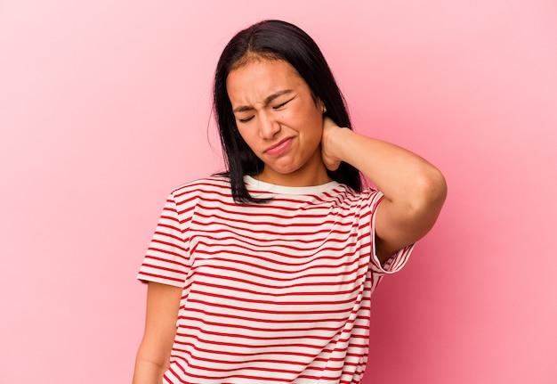 Giovane donna venezuelana isolata sul muro rosa con dolore al collo dovuto allo stress, massaggiandolo e toccandolo con la mano.