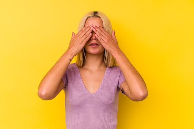 Giovane donna venezuelana isolata su sfondo giallo impaurito che copre gli occhi con le mani.