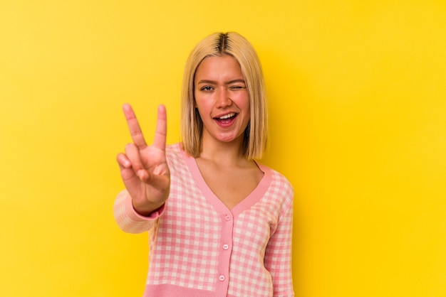 Giovane donna venezuelana isolata su sfondo giallo che mostra il numero due con le dita.