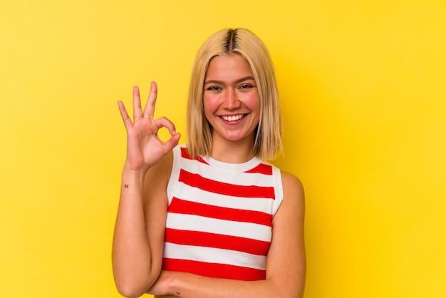 La giovane donna venezuelana isolata su priorità bassa gialla strizza l'occhio e tiene un gesto giusto con la mano.