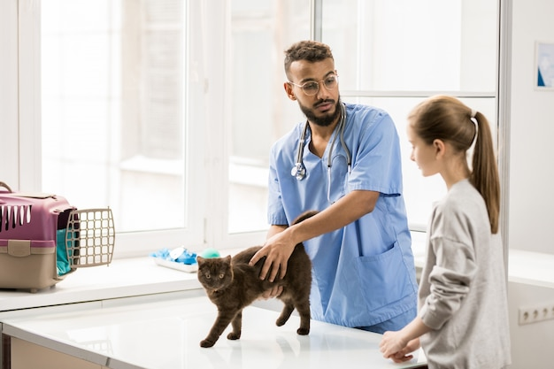 Giovane veterinario che parla con bambina mentre accarezza il gatto prima o dopo l'esame nelle cliniche