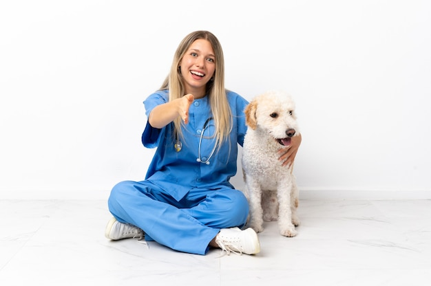Giovane donna veterinaria con cane seduto sul pavimento si stringono la mano per chiudere un buon affare