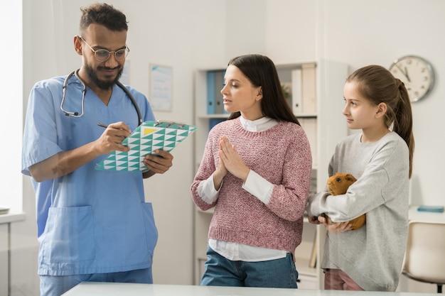 Giovane medico veterinario che fa le prescrizioni mediche per la cavia e che parla con proprietari dell'animale domestico