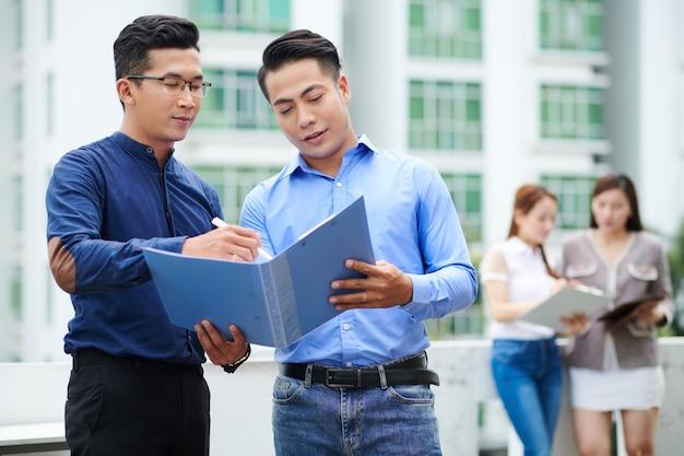 Giovani uomini d'affari vietnamiti che aprono la cartella e discutono del rapporto o del contratto all'interno