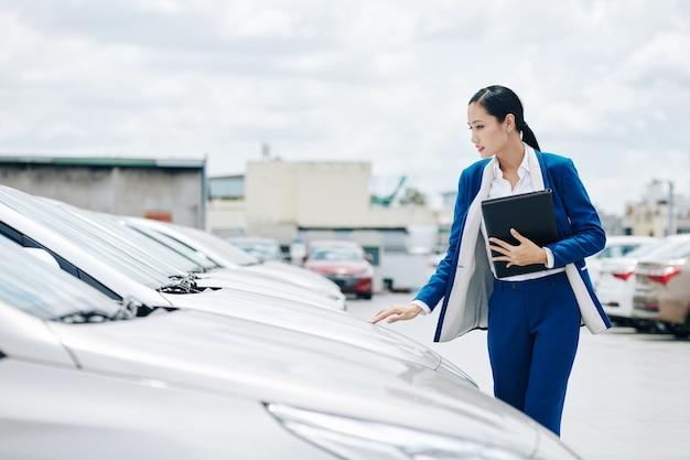 Giovane manager vietnamita di concessionaria auto che controlla le auto in vendita