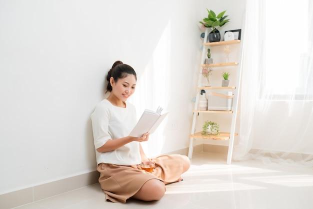 Giovane ragazza vietnamita che beve tè e legge un libro mentre è seduta per terra