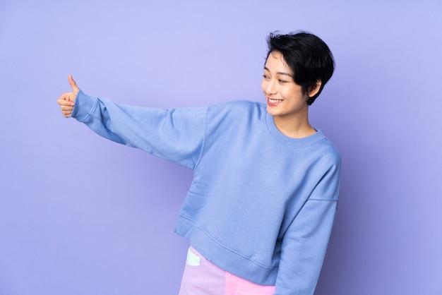 Giovane donna vietnamita con i capelli corti sul muro viola dando un pollice in alto gesto