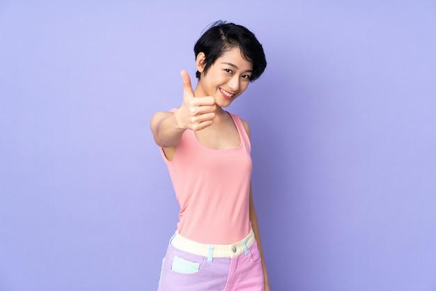 Giovane donna vietnamita con i capelli corti sul muro viola con il pollice in alto perché è successo qualcosa di buono