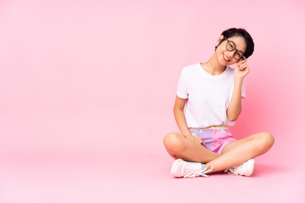 Giovane donna vietnamita con i capelli corti che si siede sul pavimento sopra la parete rosa isolata con i vetri e felice