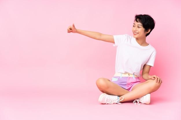 Giovane donna vietnamita con i capelli corti, seduta sul pavimento sul muro rosa dando un pollice in alto gesto