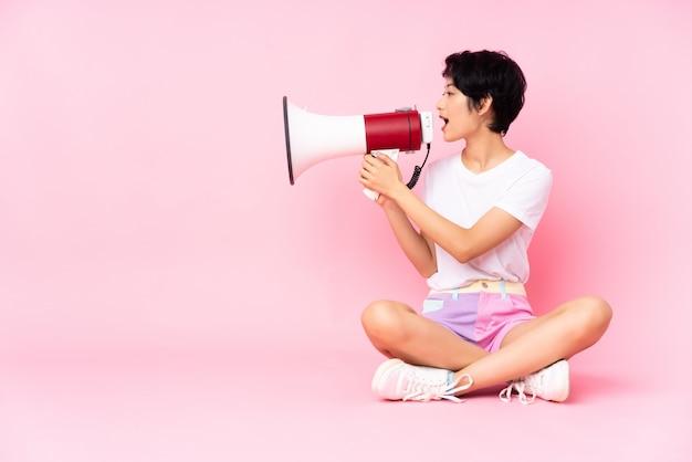 Giovane donna vietnamita con i capelli corti che si siede sul pavimento sopra la parete rosa che grida tramite un megafono