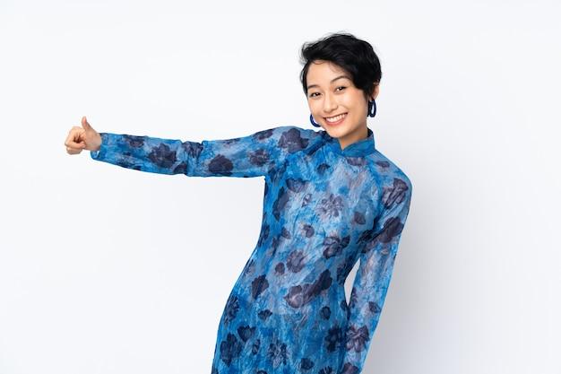 Giovane donna vietnamita con i capelli corti che indossa un abito tradizionale sul muro bianco dando un pollice in alto gesto