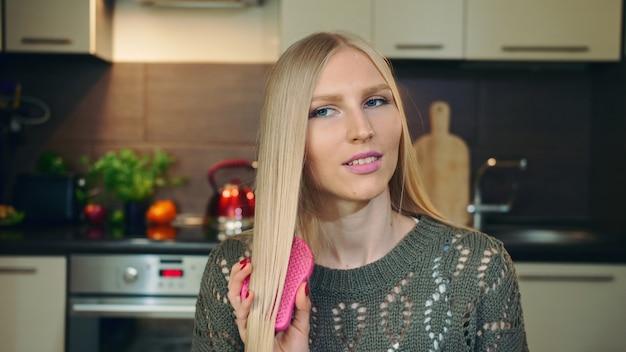 Giovane vlogger che pettina i capelli per la macchina fotografica.