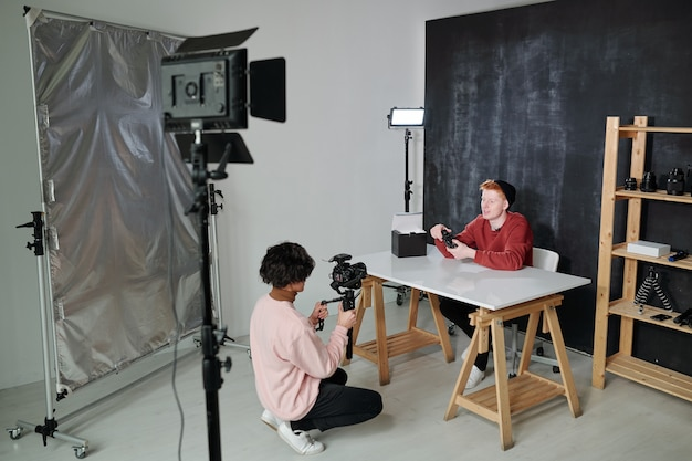 Giovane vlogger che racconta la nuova attrezzatura fotografica mentre era seduto alla scrivania davanti all'operatore con la videocamera